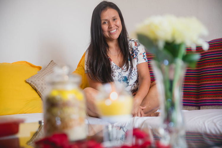 Portrait of smiling woman sitting at home