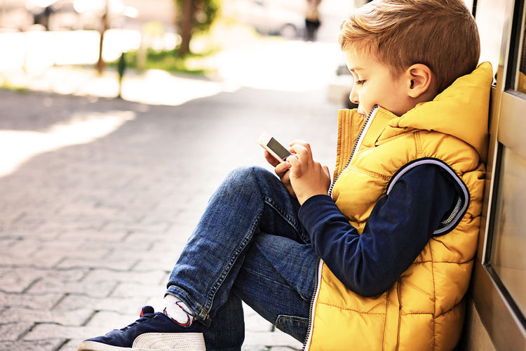 Rear view of boy sitting on mobile phone