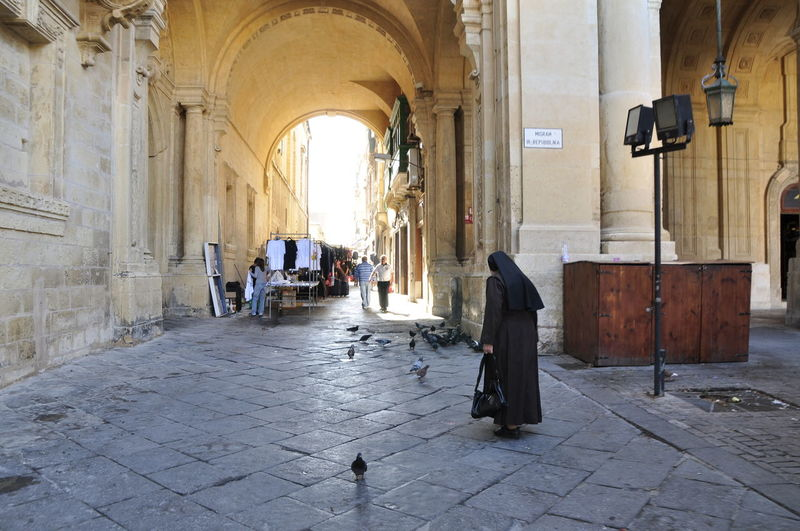 Arch City City Life Full Length Lifestyles Malta Nun Passageway Paving Stone Person Walking