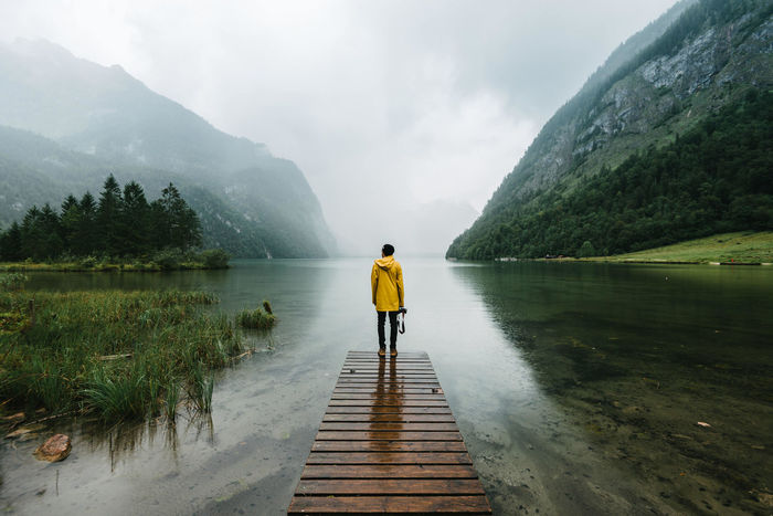 Rear view of man standing on pier over lake against mountains