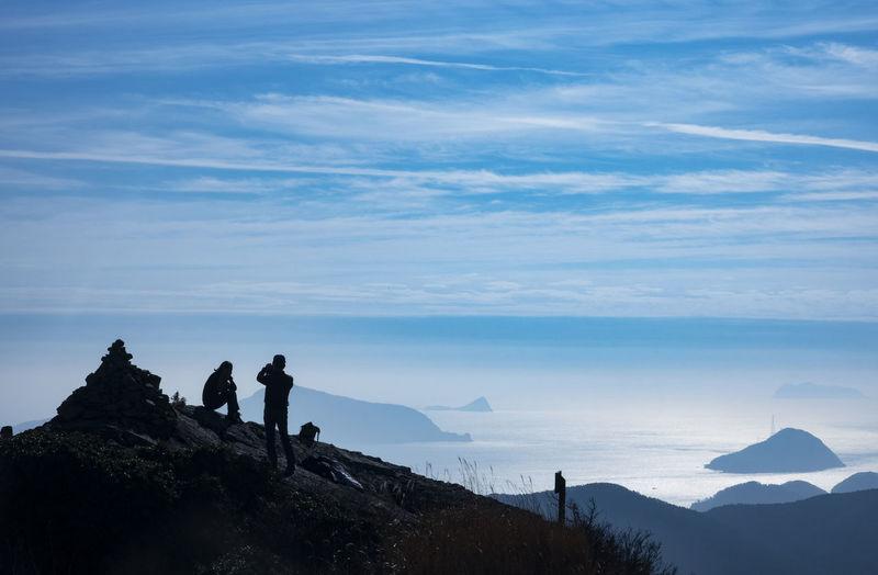 Men standing on rock against sky