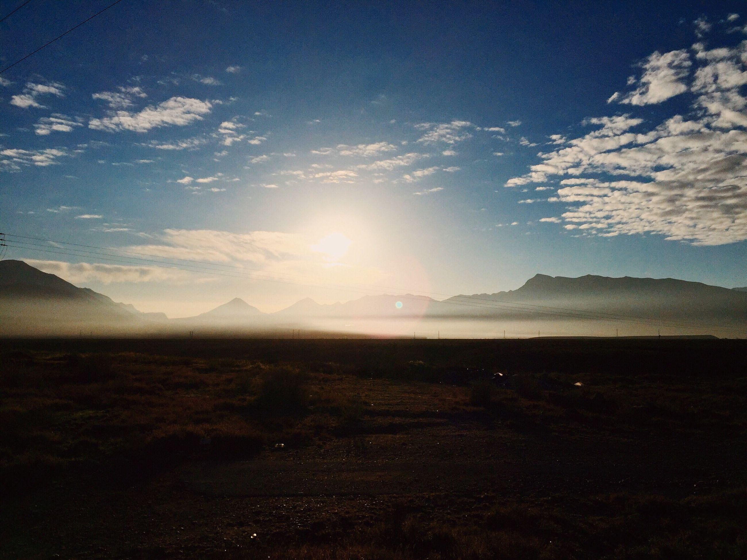 tranquil scene, mountain, tranquility, scenics, landscape, sky, beauty in nature, mountain range, nature, cloud - sky, non-urban scene, sunlight, sun, idyllic, sunbeam, cloud, horizon over land, remote, outdoors, sunset