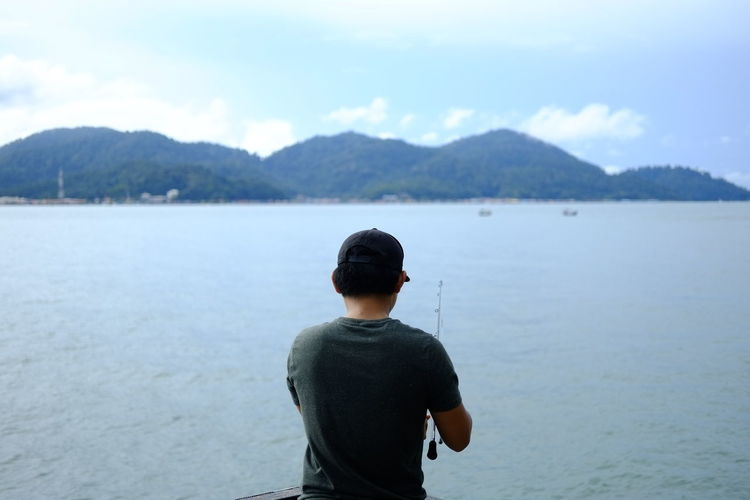 Rear view of young man fishing in sea against sky