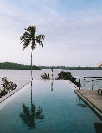 Side view of woman standing at edge of infinity pool against sky