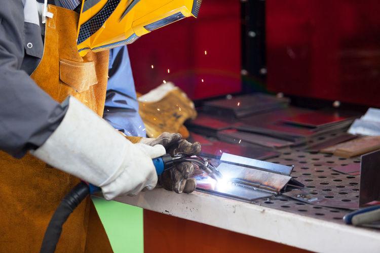 Midsection Of Male Welder Welding Metal In Factory