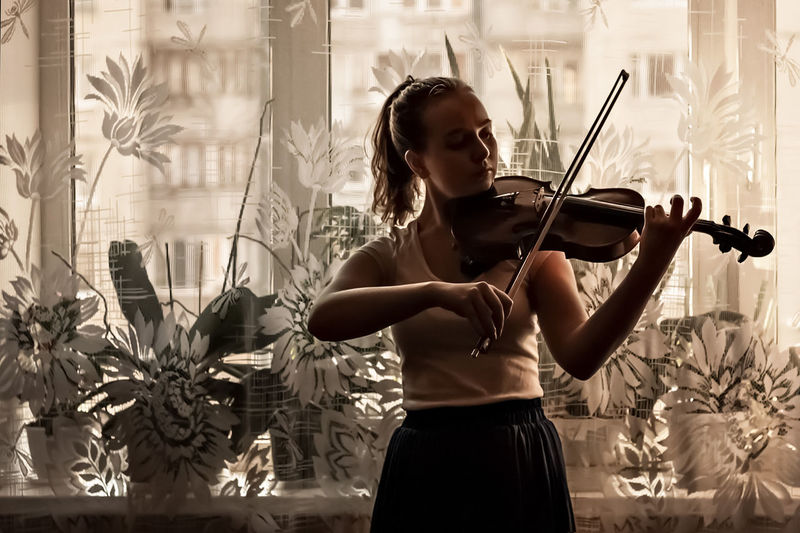 Young woman playing violin by window