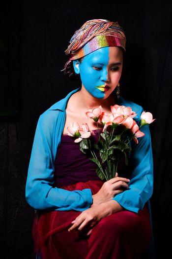 Midsection of woman wearing mask against blue wall