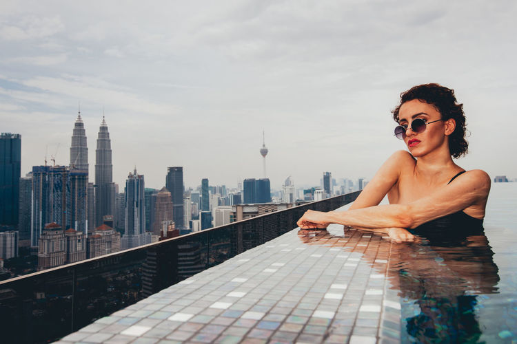 Architecture Built Structure Building Exterior One Person Real People City Sky Lifestyles Water Young Adult Adult Leisure Activity Young Women Building Nature Fashion Tower Tall - High Skyscraper Cityscape Beautiful Woman Office Building Exterior International Women's Day 2019