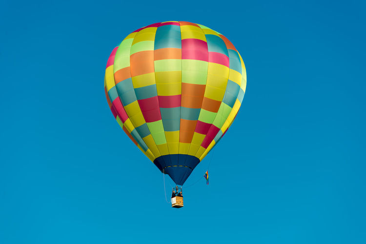 Low angle view of man and woman in hot air balloon against clear blue sky