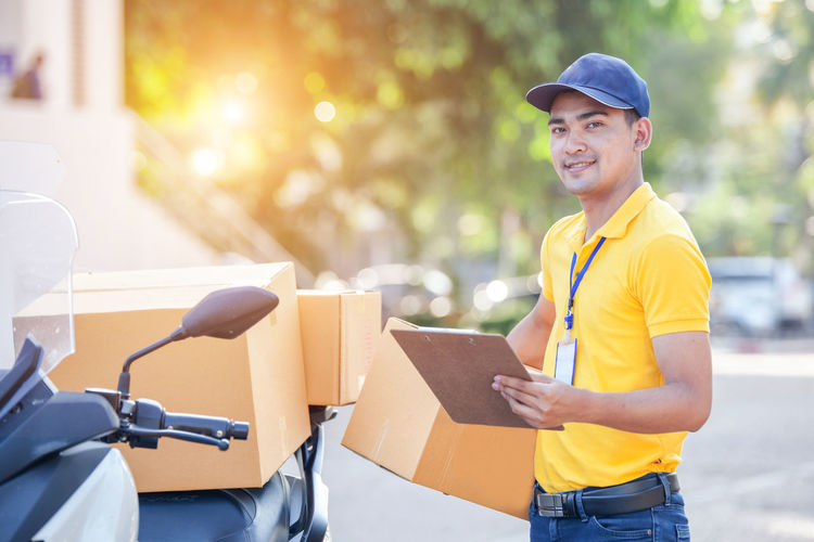 Portrait of smiling delivery person with box standing by motor scooter