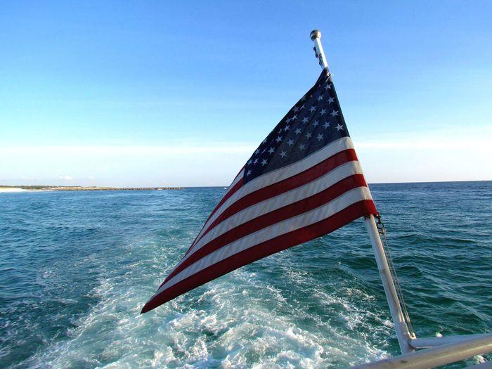 American Flag On Boat Railing Over Sea Against Blue Sky