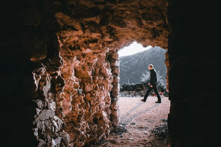 Man walking by rock formation seen through cave