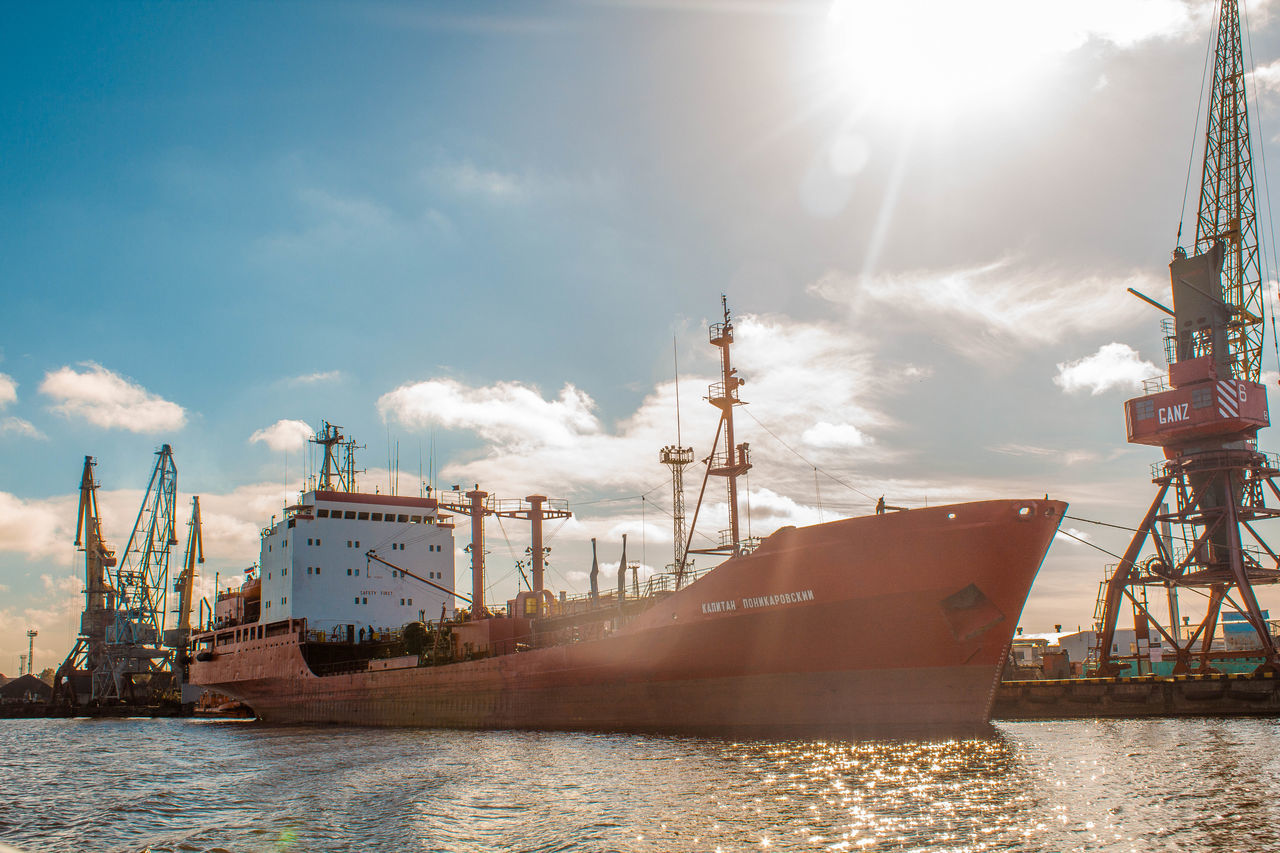 lens flare, water, sky, transportation, nautical vessel, industry, cloud - sky, no people, sunlight, day, mode of transport, freight transportation, waterfront, sun, oil industry, outdoors, sea, ship, commercial dock, harbor, nature, offshore platform, drilling rig, shipyard, oil pump