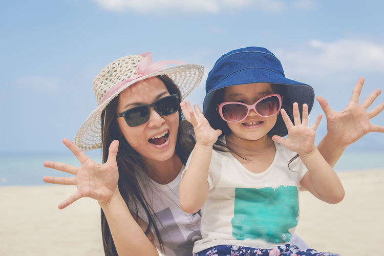 Happy mother and daughter wearing sunglasses enjoying at beach against sky