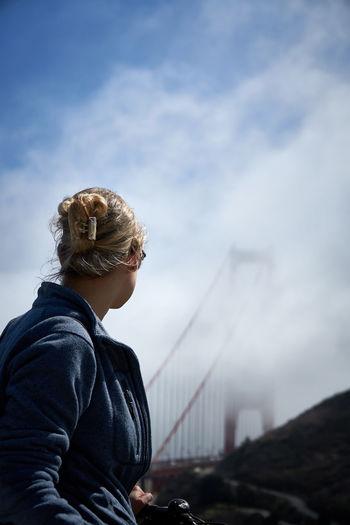 Man sitting on bridge against sky