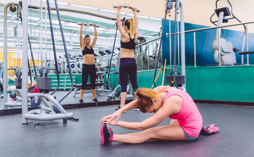 Beautiful woman stretching in a fitness center and female friend doing exercises with dumbbells in the background Athletic Exercising Females Horizontal Slim Woman Activity Beauty Club Equipment Fit Fitness Gym Healthy Lifestyle Indoors  Muscles Muscular Real People Sport Streching Train Training Two People Weight Workout