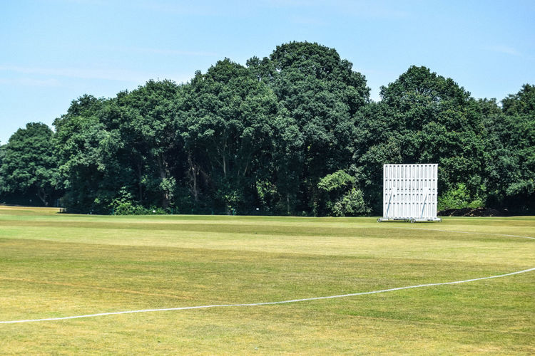 Boundary Competition Cricket Day Empty Environment Field Grass Green Color Growth Land Leisure Activity Nature No People Outdoors Outfield Playing Field Sight Screen Sky Sport Sunlight Tree