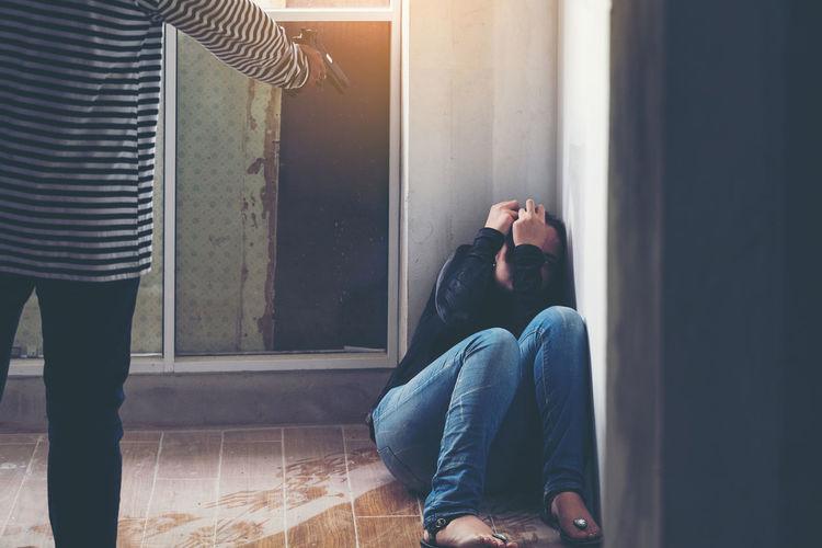 Burglar harassing pointing handgun at woman by window
