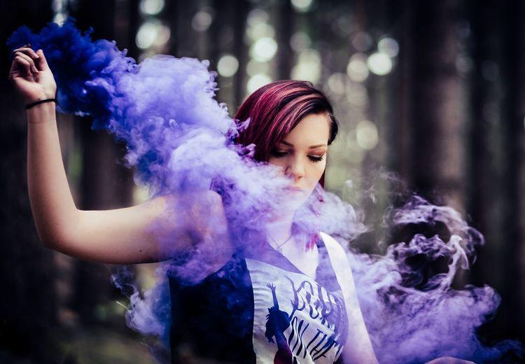 Portrait of beautiful woman holding purple outdoors