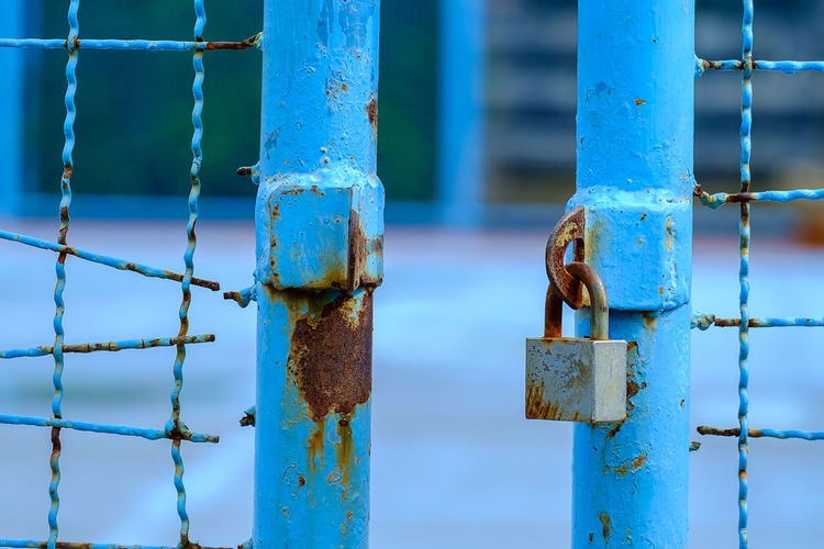 Close-up of padlock hanging on rusty fence