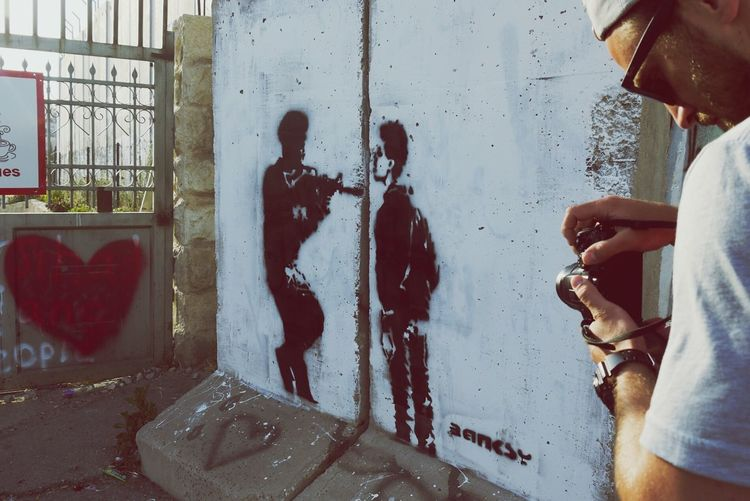 What I Value is Freedom Of Expression Taking Photos in Bethlehem Israel Palestine Banksy Photographer Street Art Fighting Injustice Adventure Buddies The Tourist Telling Stories Differently The Photojournalist - 2016 EyeEm Awards People And Places Banksyart on the Wall in Bethlahem Resist