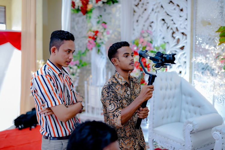 Man looking at friend filming in wedding ceremony