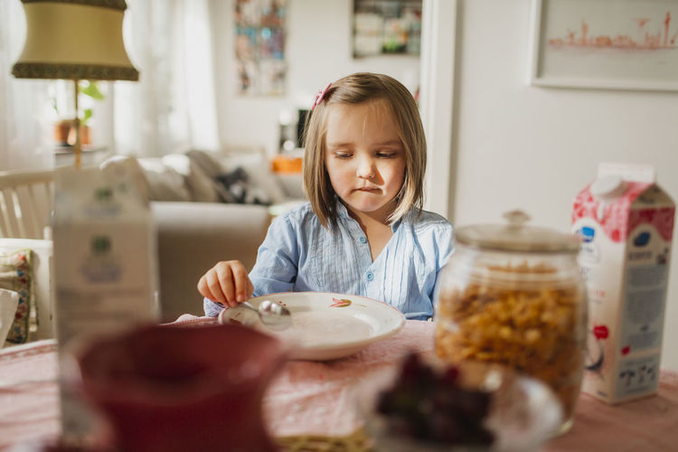 Portrait of a girl having food at home