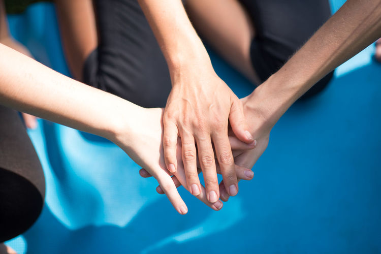 High Angle View Of Friends Huddling Hands
