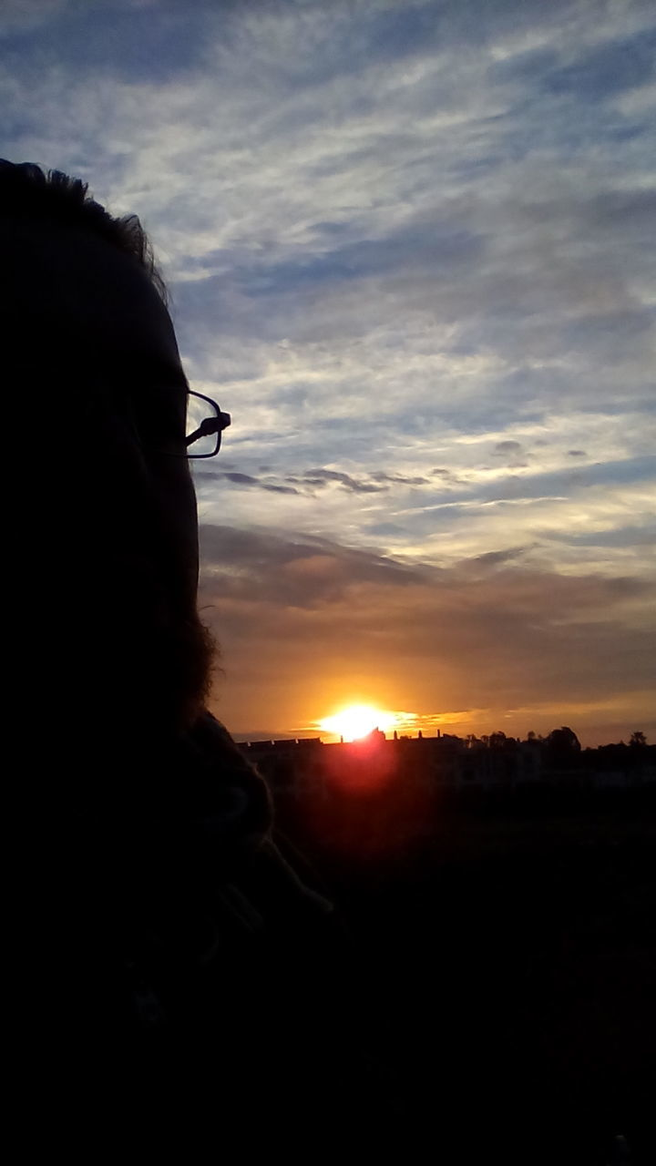 sunset, sky, silhouette, one person, cloud - sky, real people, nature, outdoors, sun, beauty in nature, scenics, eyeglasses, close-up, day, people