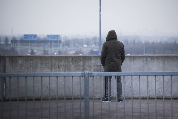 Rear view of man on railing by river in city