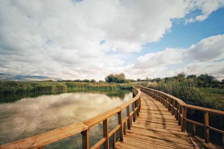 Wooden boardwalk on landscape against sky