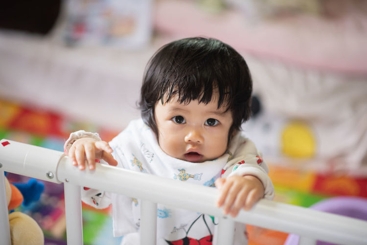Portrait of cute girl by railing in crib