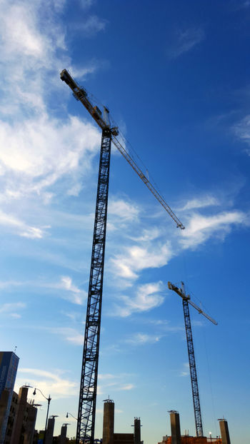 High cranes with blue sky and white clouds City City Life Cityscape Architecture Building - Activity Building Exterior Built Structure Cityscapes Construction Construction Machinery Construction Site Crane Crane - Construction Machinery Day Development High Crane Industrial Equipment Industry Low Angle View Man Made Object No People Outdoors Progress Sky Vertical