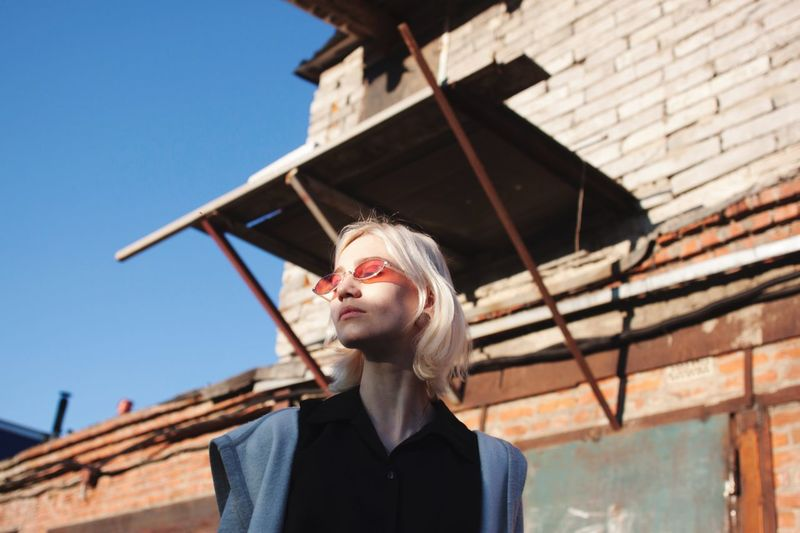 Low angle portrait of young woman against building
