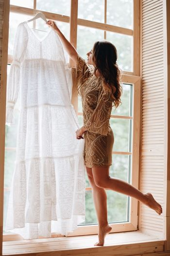 Woman holding wedding dress while standing against window