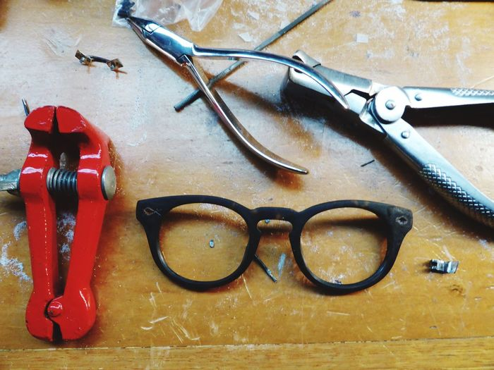High Angle View Of Damaged Eyeglasses By Pliers On Table In Workshop