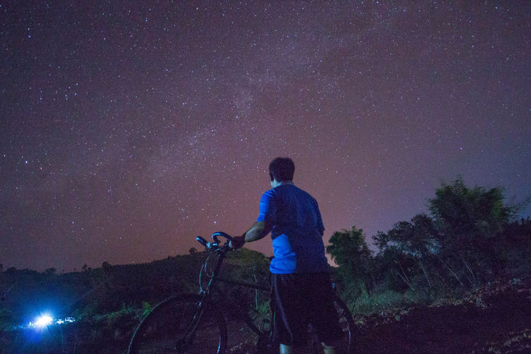 Rear view of man with bicycle against star field at night