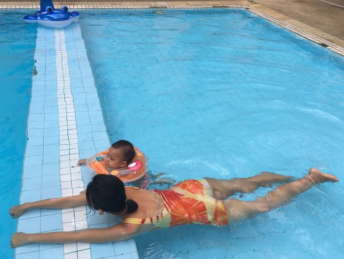 High angle view of mother with daughter swimming in pool