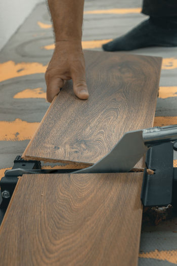 hand holding and cutting the laminate panel with a laminate cutter Laminate Cutter Cutting Board Cutting Holding Occupation Working Worker Human Hand Human Body Part Board Panel Work Craftsperson Wood - Material Skill  Hand Home Renovation Laminate Flooring Floor Male Man Tool Work Tool