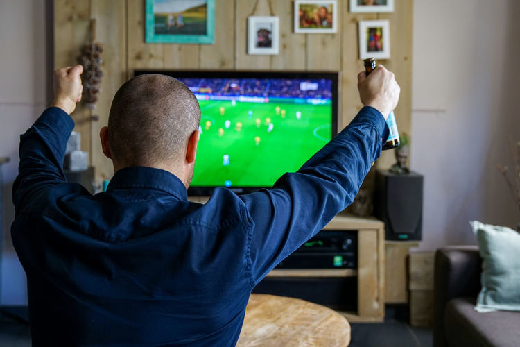portrait of man watching an important soccer match at home. cheering for the team Technology One Person Rear View Indoors  Adult Men Looking Arms Raised Television Set Watching Tv Connection Communication Cheering Soccer Enjoy At Home Interior Beer Beer Bottle Drink World Cup European Championship  Soccer Leage Match Body Part
