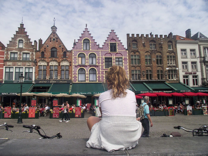 Rear view of woman on street against buildings in city