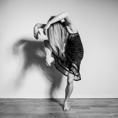 Side view of woman dancing on floor against wall