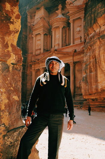 Portrait of mature man standing at historical building at petra