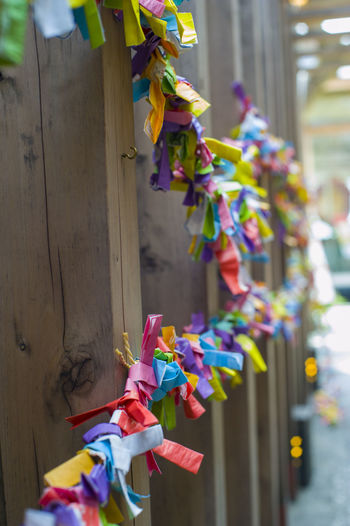 Close-up of multi colored tied hanging on clothesline against building