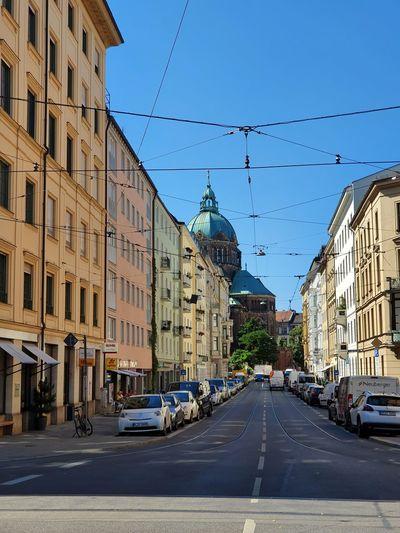 Cars on city street by buildings against clear blue sky