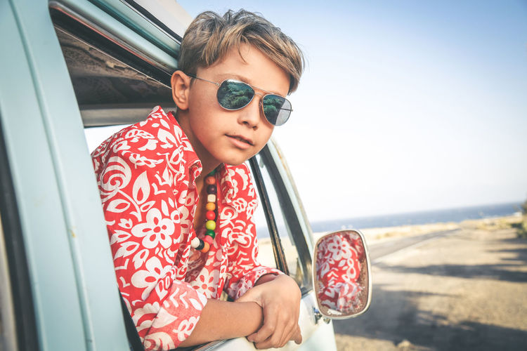 Handsome teenage boy with sunglasses posing charming out the window of a vintage van dressed as a flower hippie child. Concept of freedom and lighthearted holiday, free time trendy vintage traveling. One Person Glasses Real People Child Leisure Activity Lifestyles Childhood Casual Clothing Waist Up Day Sunglasses Nature Females Sitting Portrait Holding Fashion Looking Outdoors Innocence