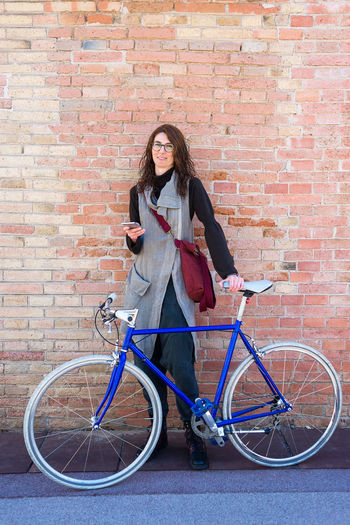 Full length of woman with bicycle against brick wall