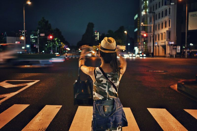 Rear View Of Woman Photographing On City Street At Night