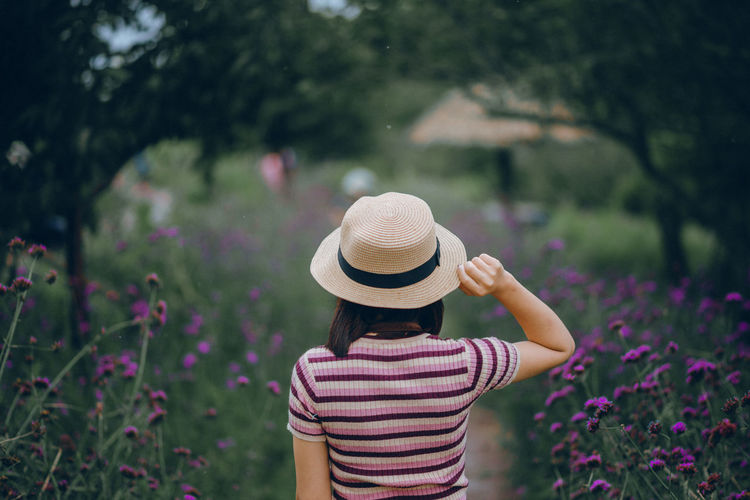 Midsection of woman wearing hat against plants