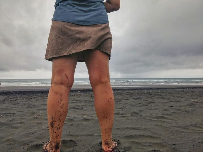 Low section of woman with dirty legs standing at beach against cloudy sky